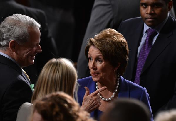 House Minority Leader Nancy Pelosi (D-Calif.) confers on the House floor prior to President Obama's State of the Union address.
