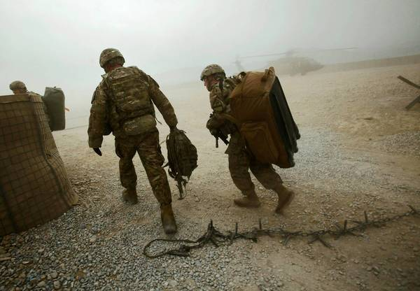 U.S. troops wait to be transported by helicopter at Forward Operating Base Naghlu, outside Kabul, Afghanistan.