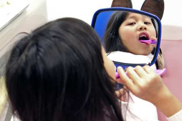 Lucy Fung, 7, inspects the work at the Kids Community Dental Clinic in Burbank last week. This month the clinic is offering free dental screenings for children under age 18.