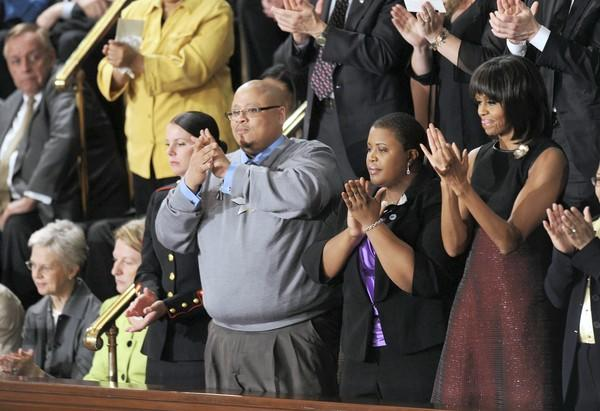 Nathaniel Pendleton Sr. and Cleopatra Cowley-Pendleton stand next to First Lady Michelle Obama as they applaud President Obama's State of the Union address. Their daughter Hadiya was killed two weeks ago in Chicago.