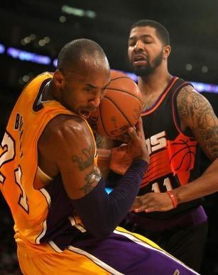 Kobe Bryant loses control of the ball as Phoenix forward Markleff Morris stands over him.