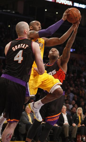 Lakers guard Kobe Bryant drives the lane against Phoenix's Marcin Gortat and P.J. Tucker.