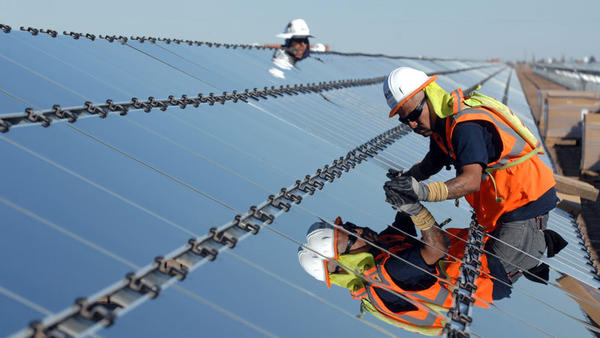 A worker installs a solar panel module at the Imperial Solar Energy Center South project near Seeley on Tuesday.