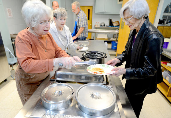 Marjorie Christie, left, and Jane Dufourny, center, serve pancakes and sausage gravy Tuesday night to Anna Crowell of Martinsburg, W.Va., at Trinity Episcopal Church in Martinsburg. The church was hosting its annual Mardi Gras Pancake Supper for Shrove Tuesday.