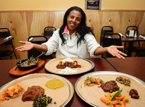 At Mariam's Restaurant co-owner Beleteshachew Mulata sits with several of her culinary creations which are popular items on her menu. There are several vegetarian items on the menu which includes Ethiopian and American cuisine.