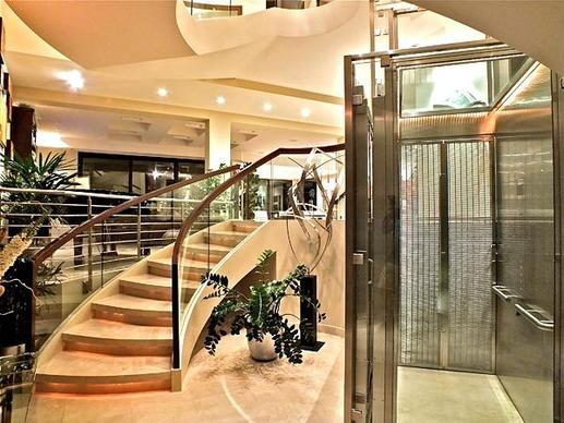 A stainless-steel-and-glass elevator is a focal point at a three-level contemporary in Naples listed at $6.75 million.