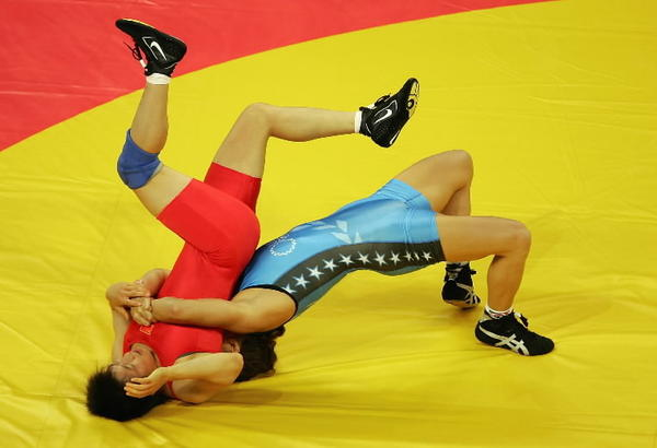 Sara McMann (blue) of the USA flips Lili Meng of China during the women's Freestyle wrestling 63 kg elimination round on Aug. 22, 2004, during the Athens 2004 Summer Olympic Games.