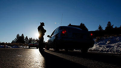 A California Highway Patrolman stops motorists from driving further down Highway 38 near Big Bear on Wednesday morning.