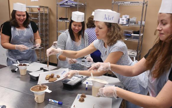 "Juliet Krummick, middle, carefully uses a stick to drizzle milk chocolate as others watch during a ""Mom's Chocolate Party"" at Farris and Foster's Famous Chocolate Factory in Waterford Towers in Orlando on Thursday, February 7, 2013."