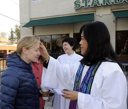 The Rev. Cristina Paglinauan, associate rector at the Church of the Redeemer, gives ashes to Leta Dunhanm of Baltimore outside the Starbucks on Roland Avenue.
