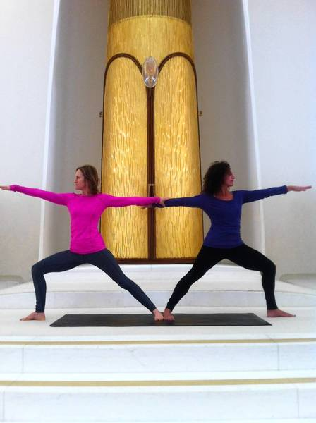 Instructors Stephanie Adler, left, and Lauri Stern demonstrate one of the poses that will be intergrated into North Shore Congregation Israel's upcoming Shabbat ShalOHM.