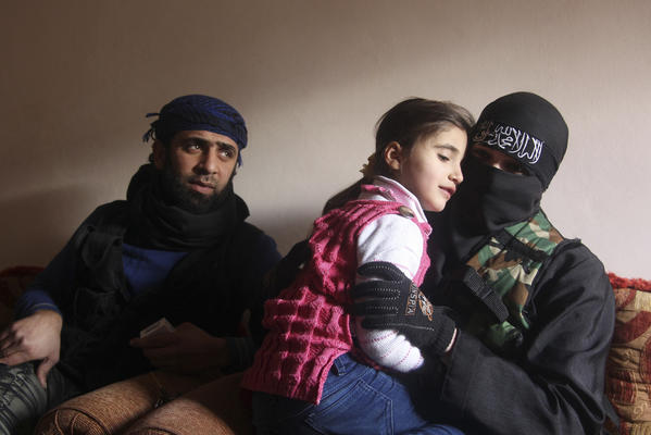 Um Jaafar, a woman fighter in the Free Syrian Army, sits with her husband Abu Jaafar, a Sawt al-Haq (Voice of Rights) battalion commander, and her daughter Faten at their home in Aleppo. Um Jaafar was a women's hairdresser before the revolution and after being trained by her husband, she is now a member of a Sawt al-Haq battalion on the frontline of Aleppo's Sheikh Saeed neighborhood.