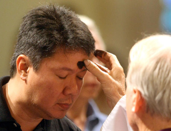 Father Jeremiah Singleton, pastor of St. Anthony Church administers ashes to the forehead of Francis Reyes.  On Ash Wednesday, the first holy day since Pope Benedict made his momentous retirement announcement, Catholics buttonholed outside church praise or criticize his decision to leave on the eve of Lent, an important holy season.