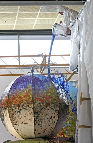 "An assistant pours paint on a spinning globe during the ""activation"" of ""Painting with Two Balls,"" 1997/2013, at the Orange County Museum of Art. This work is part of the artist's retrospective ""Ain't Painting a Pain"" at the museum from Feb. 17 to May 5."
