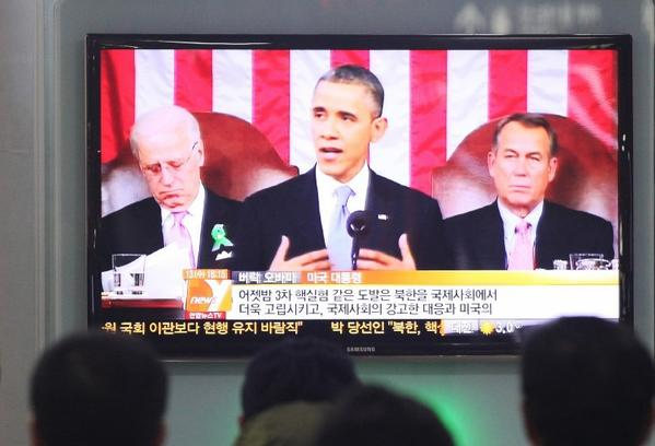 South Koreans watch a television news report on President Obama's State of the Union address at Seoul Railway Station.