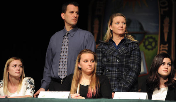 (L to R) Sarah Kazmierski, a field hockey player at Emmaus High School; Taylor Iobst, a swimmer and Kassidy Green, a field hockey player, listen to coaches speak at the signing day for Division I athletes at Emmaus High School on Wednesday.