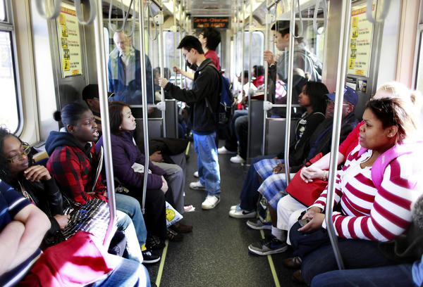 "Commuters sit in face-to-face in a new series 5000 ""L"" car on the red line."