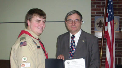 Cole McGunigale is being presented a commendation by Commissioner John Vatavuk.