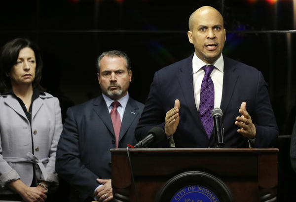 Newark Mayor Cory Booker responds angrily at a news conference regarding a video showing a naked young man being whipped because of his father's debt.