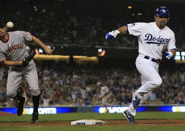 Money can't necessarily buy chemistry, according to Giants first baseman Brandon Belt, left, unable to make the play on Dodgers base runner Aaron Miles in a past meeting.