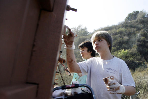 Max Doyle, 12, left, Charles Give, 13, and other members from the Boys Scout Troop 209 paint the fire warning sign in Burbank on Saturday, December 8, 2012.