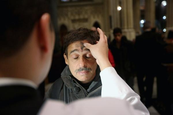 A man receives a cross of black ashes on his forehead on Ash Wednesday at St. Patrick's Cathedral in New York.