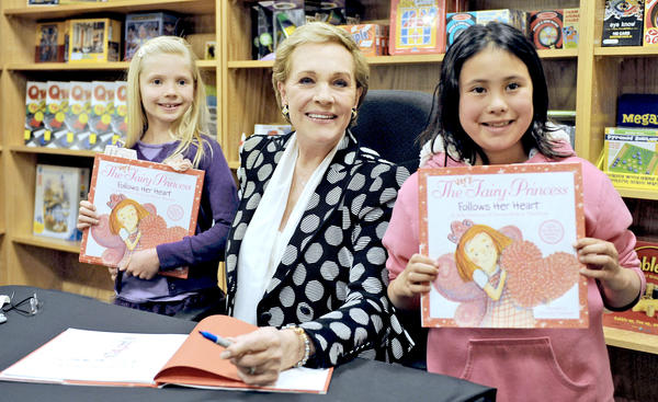 7 year-old Ava Selway, left awaits as Julie Andrews, center, signs 8 year-old Nina Blanco, right, children's book, 'A Very Fairy Princess Follows Her Heart' for at Flintridge Bookstore & Coffeehouse in La Canada, Calif.