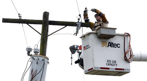 A Duke Energy worker repairs a line after a storm. The company has written off a $10-million line of credit it guaranteed to help produce the Democratic National Convention.