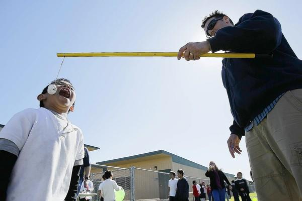 Edwin Ruiz, 6, attempts to eat a donut hanging off the end of a string held by Glenn Atkins at Rea Elementary School in Costa Mesa on Wednesday. The students put on a carnival in partnership with the Irvine charity Team Kids.