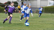 Sophia Harmon eludes Cerritos players as teammates Niki Serrano and Lindsay Rule look on. The Blue Crushers finished third at the Section 11 U-10 tournament by defeating the Goal Getters, 3-2, Sunday.