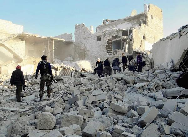 Syrian rebels stand in the rubble of buildings after reported government airstrikes near Aleppo's international airport.