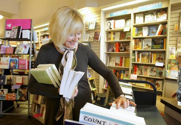 Proprieter Jane Hanauer organizes newly arrived books for shelving at Laguna Beach Books on Tuesday.
