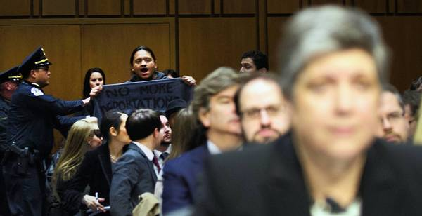 "A protester holds a banner that reads ""No More Deportations"" at a Senate committee hearing featuring Homeland Security Secretary Janet Napolitano, foreground."