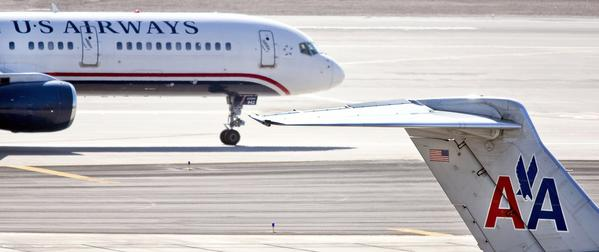 A US Airways jet taxis past an American Airlines jet parked at the gate at Sky Harbor International Airport in Phoenix.