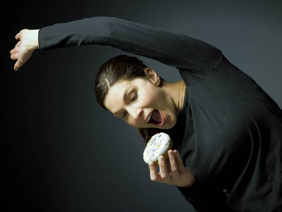 Woman stretching and about to eat donut