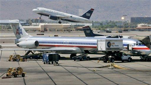 In this 2008 file photo, a US Airways jet takes off as an American Airlines jet is prepped for takeoff at Sky Harbor International Airport in Phoenix. The merger of US Airways and American Airlines has given birth to a mega airline with more passengers than any other in the world.