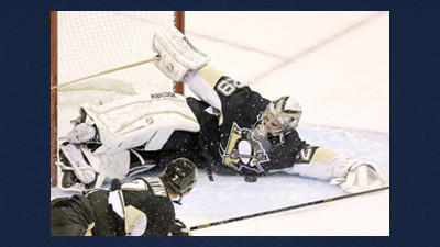 Pittsburgh Penguins goalie Marc-Andre Fleury (29) makes a sprawling save with the help of defenseman Paul Martin (7) during the first period of an NHL hockey game against the Ottawa Senators in Pittsburgh on Wednesday.