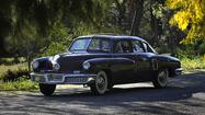 Martyn Donaldson leans hard against the hulking 1948 Tucker 48 and rolls it out of his small restoration shop in Pacoima.