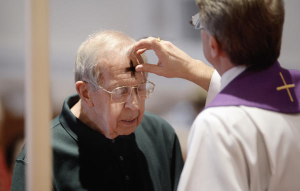 The Rev. Michael Louia marks Bill Renner's forehead with a cross of ashes during the Ash Wednesday service at St. Paul's Evangelical Lutheran Church in Funkstown.