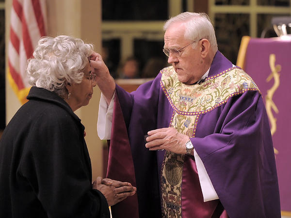 Mary Jo Blair receives ashes on her forehead Wednesday night from the Rev. Joseph L. Stahura during an Ash Wednesday service at St. Mark the Evangelist Roman Catholic Church in Greencastle, Pa.