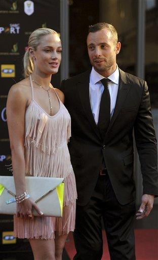 In this Nov. 4, 2012, photo, South African Olympic athlete Oscar Pistorius and girlfriend Reeva Steenkamp are pictured at an awards ceremony in Johannesburg, South Africa. Pistorius was charged Thursday in Steenkamp's murder.