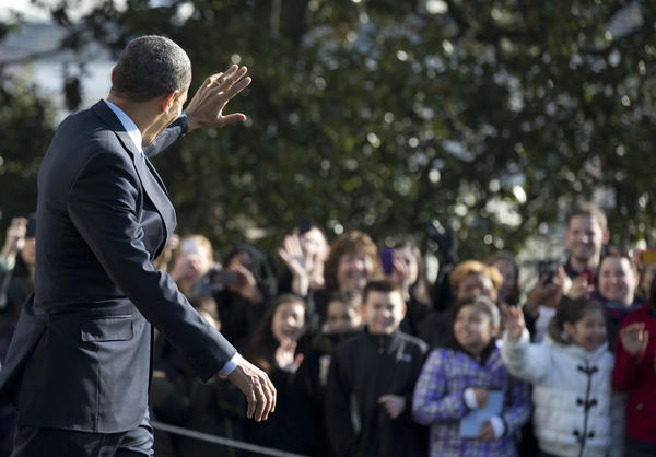President Obama waves to White House visitors.