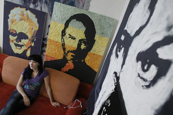 Anna-Sofiya Matveeva poses near portraits of late Apple co-founder Steve Jobs (C) and singer Elton John (L), made of chewed gum. The artist uses gums chewed by her acquaintances, as a creation usually requires from five hundred to one thousand chewed gum