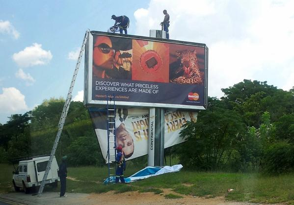 Workers take down a billboard of Olympic athlete Oscar Pistorius endorsing a product in Johannesburg, South Africa, hours after he was charged with murder.