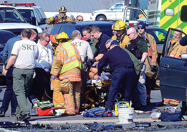 Emergency personnel attend to a person injured in a head-on crash Thursday afternoon on Interstate 81 at the U.S. 40 interchange.