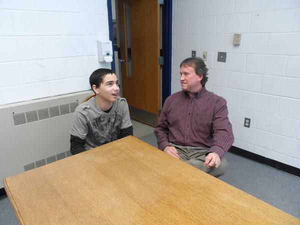 Seventh-grade Orion Center student Tyson Scott discusses what he did on his snow day with principal Doug Marvin.