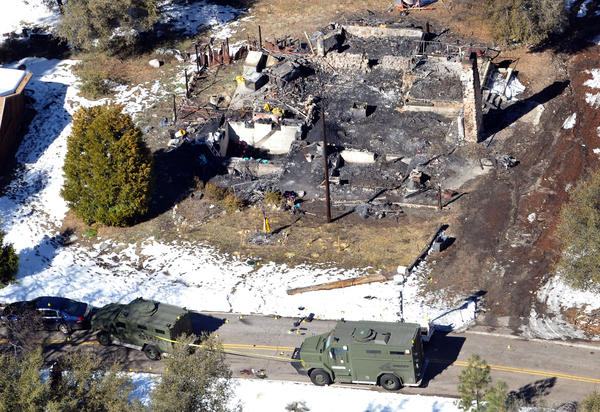 Law enforcement authorities investigate the burn-out cabin on Wednesday where accused quadruple-murder suspect Christopher Dorner was believed to have died after barricading himself inside.
