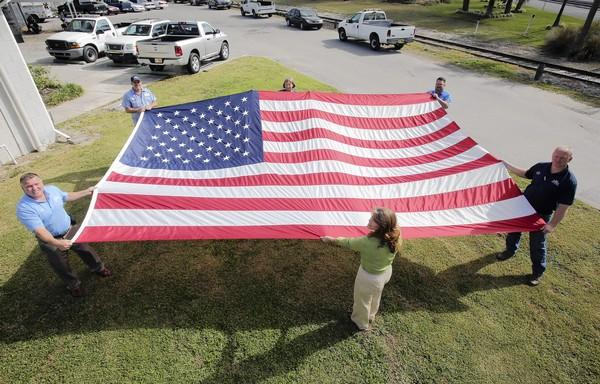 Chris Thompson, clockwise from left, Rick Payne, Cindy Solomon, Jeff Henderson, Jerad Purvis, and Jocelyn Horsley, hold a giant flag. The city of Tavares will dedicate the Freedom Flag on the new roundabout on Main Street and Sinclair Avenue on Saturday.
