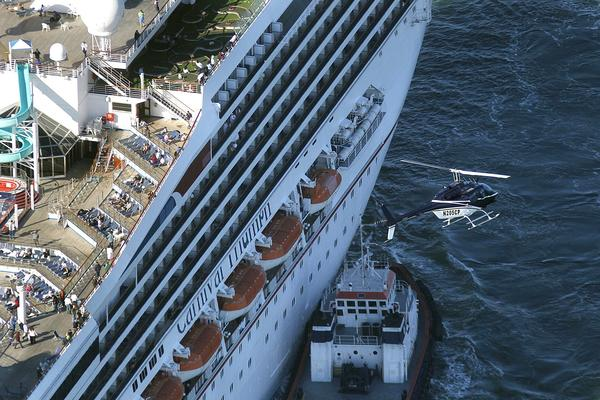 A helicopter flies above the disabled Carnival Cruise Lines ship Triumph as it is towed to Mobile Bay, Ala.