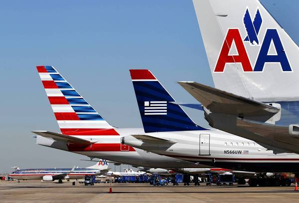 A US Airways plane is parked between two American Airlines planes, one bearing the new logo, far left, and the old logo, far right.